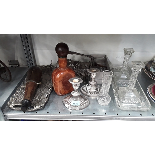 1035 - A pair of silver plated squat candlesticks, glass candlesticks with tray, leather bottle and other c...