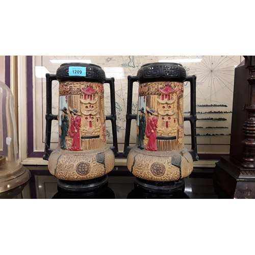1209 - A pair of oriental style twin handled plaster vases....