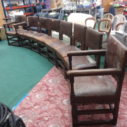 2388 - A set of eight vintage oak framed studded leather chairs to include two carvers....