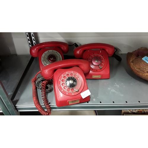 1042 - Three vintage red telephones ....