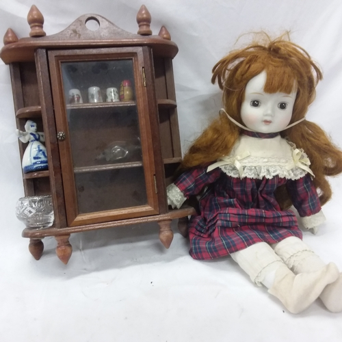 1025 - A china doll together with with a cabinet and a selection of Beatrix Potter books....