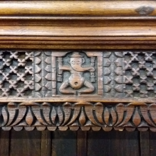 1403 - A carved hardwood open fronted four shelved bookcase....