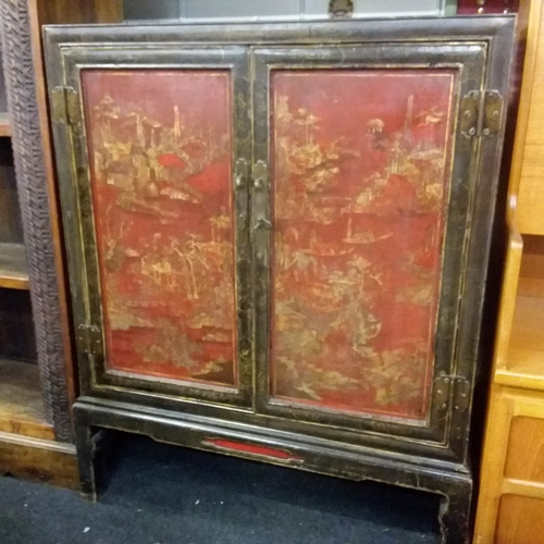1404 - A Chinese double cabinet with two red lacquered pictorial doors....