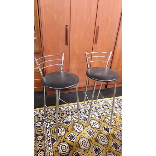 1467 - A pair of chrome bar stools with backs and black leather seat pads....