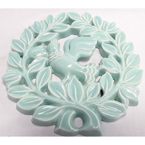123 - Poole Pottery shape 312 pierced wall plaque of a dove within garlands of leaves in pastel green glaz...