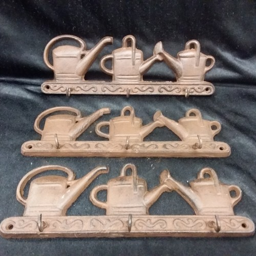1148 - Three sets of cast iron toolset hooks depicting watering cans.(174)....