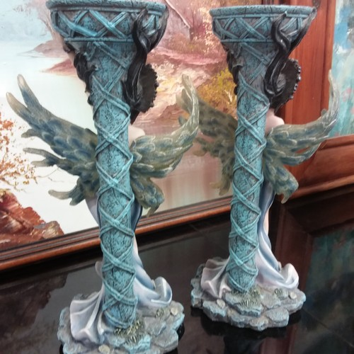 1016 - A pair of modern resin candlestick holders depicting mermaids....