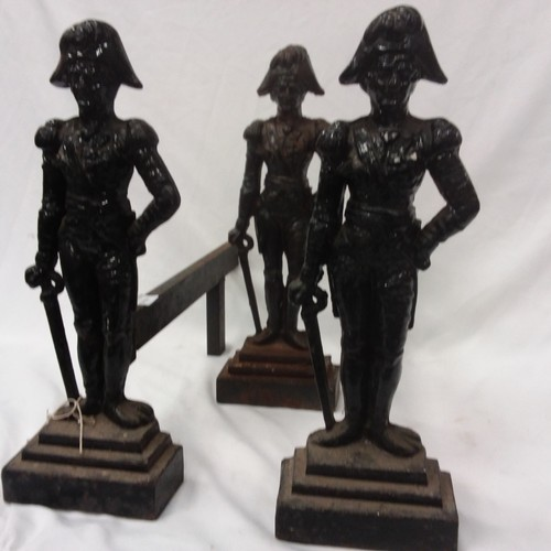 1118 - A pair of cast iron fire dogs together with a cast iron front piece depicting soldiers....