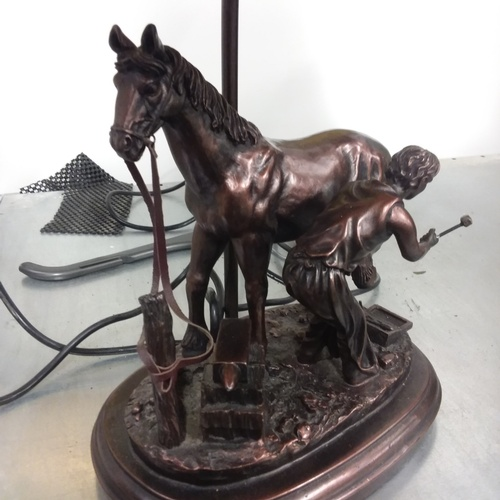 1172 - A resin table lamp depicting a blacksmith shoeing a horse....