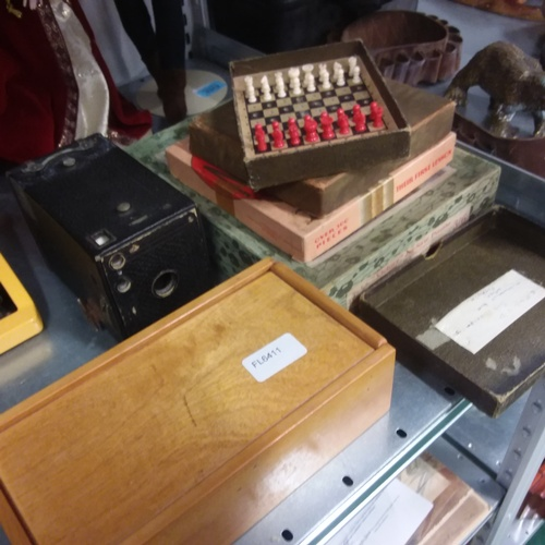 1199 - A box of vintage chess travel set, puzzles and camera together with a box of wooden chess pieces....