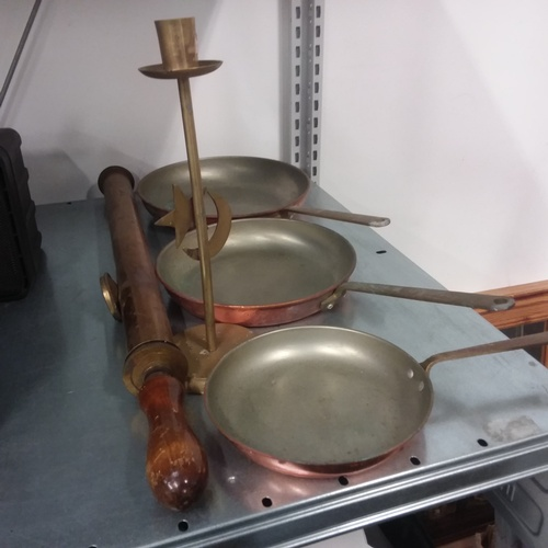 1208 - A brass vintage sprayer and candlestick together with a set of three copper skillets....