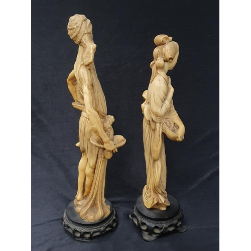 1251 - A pair of carved bone oriental figurines on wooden bases....