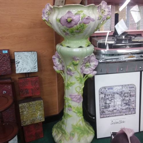 1377 - A large decorative ceramic jardiniere stand with planter in a floral pattern....