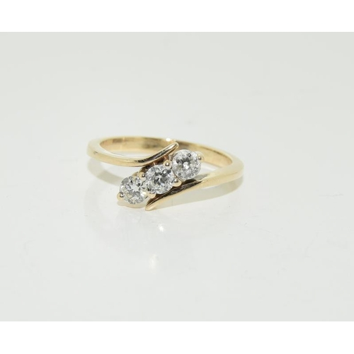 457 - 18ct yellow gold three stone Diamond cross over ring - 60 points approx. Size M....