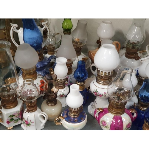1044 - A large collection of assorted miniature oil lamps....