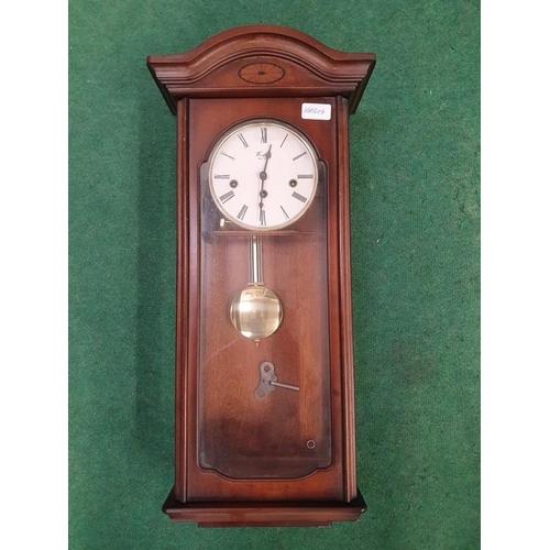 1118 - A modern mahogany wall hanging clock....