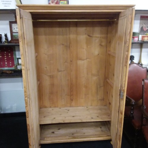 1134 - A vintage pine double wardrobe resting on bun feet....