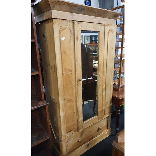 1139 - A vintage pitch pine wardrobe with mirror to centre....