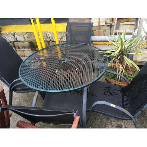 2004 - A round metal outdoor table with four plastic weave chairs....