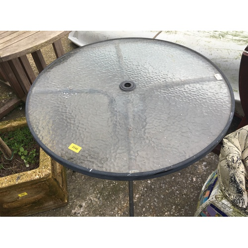 2046 - A glass topped round outdoor table....