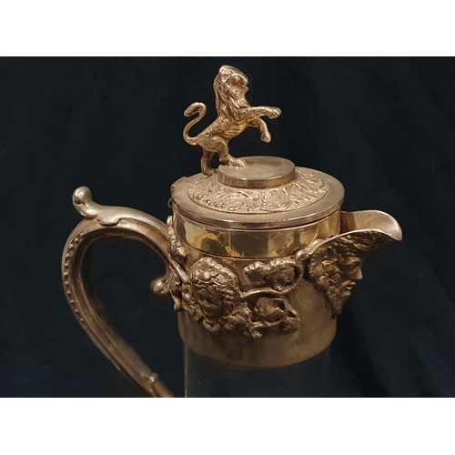 69 - A Victorian glass claret jug with silver plated handle and lid. Lion statue and other decoration to ...