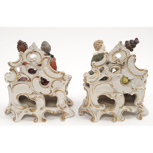 21 - Pair of porcelain figures in romantic settings showing possibly Derby back marks....