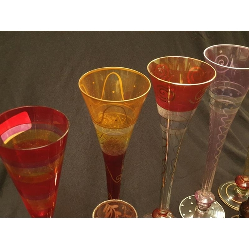 28 - A collection of five coloured patterned stemmed glasses together with a pair of smaller coloured gla...