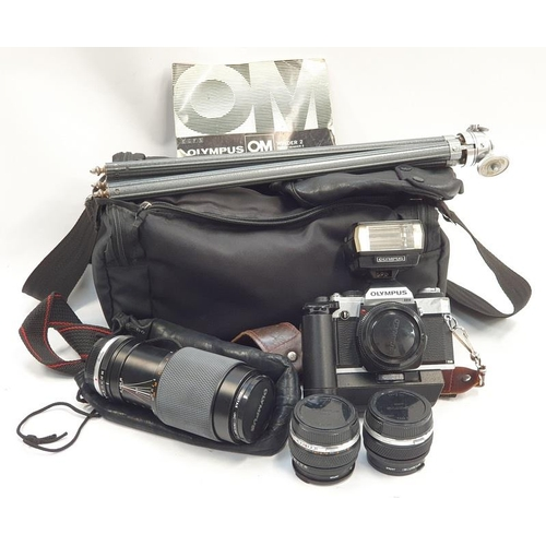 392 - Vintage Olympus OM-20 35mm camera together with a collection of lenses and accessories....