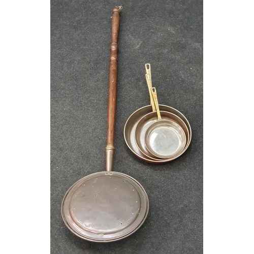 419 - A bed warming pan and a set of copper frying pans.