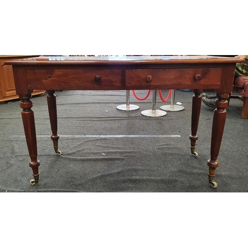 1446 - Victorian mahogany two drawer writing desk on turned supports with porcelain castors....