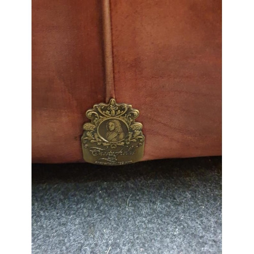 1447 - Three seater leather Chesterfield settee with Chesterfield badge....