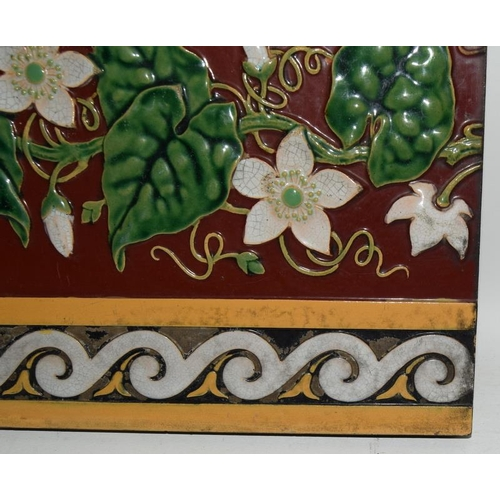 283 - Minton Hollins moulded majolica dado tile depicting white clematis on a burgundy ground with white &...