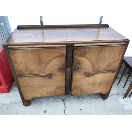 601 - A WALNUT SIDEBOARD WITH TWO DOORS (ONE SLIGHTLY WARPED)...