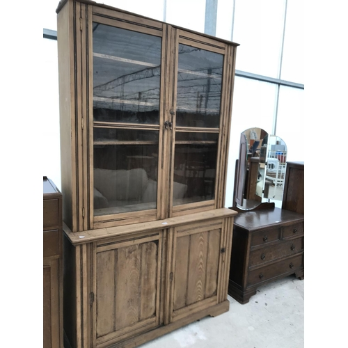 606 - A PINE CABINET WITH TWO LOWER DOORS AND TWO UPPER GLAZED DOORS...