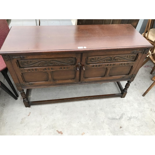 633 - A PRIORY STYLE OAK SIDEBOARD WITH TWO DOORS AND LOWER STRETCHER RAILS...