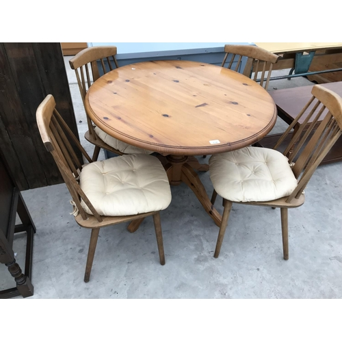 634 - A CIRCULAR PINE DINING TABLE AND FOUR ERCOL STYLE DINING CHAIRS...