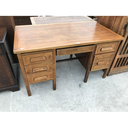 643 - AN OAK DESK WITH CENTRE DRAWER AND FIVE OUTER DRAWERS...