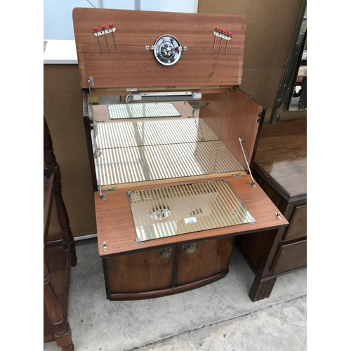 666 - A RETRO 1950s WALNUT AND TEAK COCKTAIL CABINET WITH CONCERTINA FALL FRONT AND RAISED TOP, MIRRORED I...