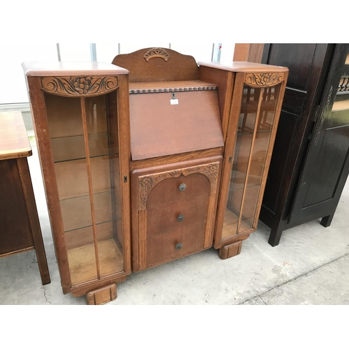 670 - AN OAK BUREAU CABINET WITH FALL FRONT, THREE DRAWERS AND TWO GLAZED SIDE DOORS...