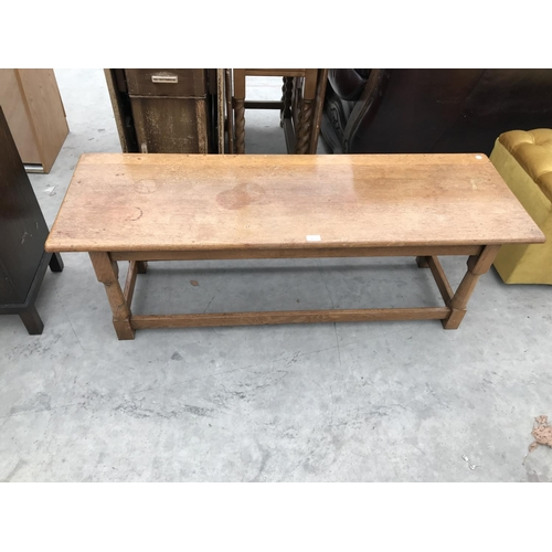 702 - A RECTANGULAR OAK COFFEE TABLE WITH LOWER STRETCHER RAILS...