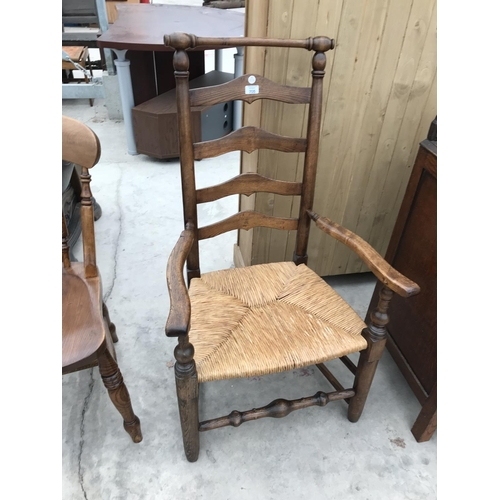 705 - A HIGH LADDER BACKED OAK ARMCHAIR WITH RUSH SEAT...