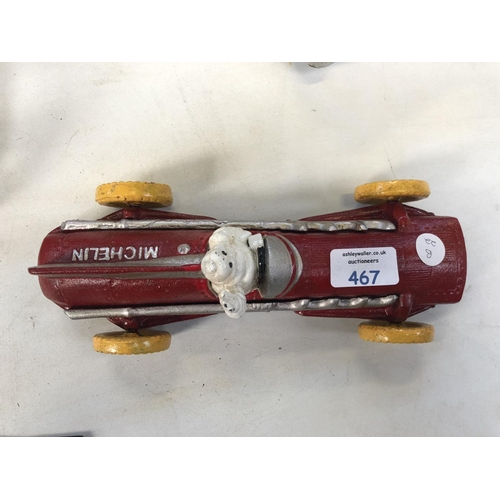 467 - A CAST IRON MODEL OF THE MICHELIN MAN IN RED RACING CAR...