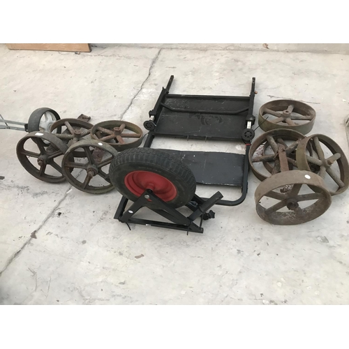 112 - NINE VINTAGE CAST IRON WHEELS, THREE AXLES AND A WHEELBARROW...