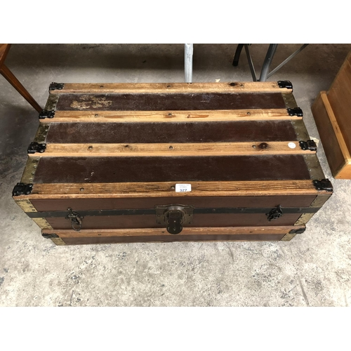 327 - A WOODEN TRAVELLING METAL BOUND STORAGE TRUNK...