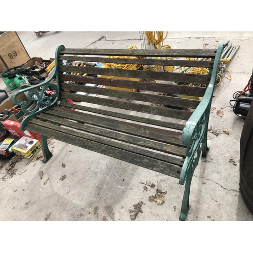 26 - A GREEN WROUGHT IRON AND WOODEN SLATTED GARDEN BENCH...