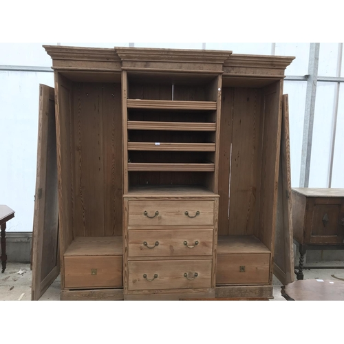 604 - AN ANTIQUE THREE SECTION STRIPPED PINE WARDROBE 202CM WIDE X 223CM HIGH X 50CM DEEP, 4 CENTRAL SLIDE...