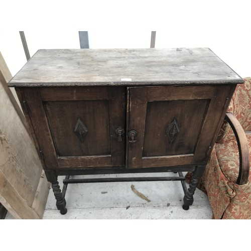 605 - AN OAK SIDEBOARD WITH TWO DOORS AND BARLEY TWIST SUPPORTS...