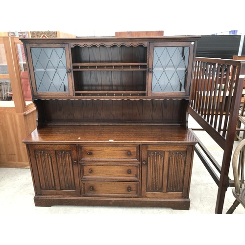 639 - AN OAK OLD CHARM STYLE DRESSER WITH TWO LOWER LINEN FOLD DOORS AND THREE DRAWERS AND UPPER PLATE RAC...