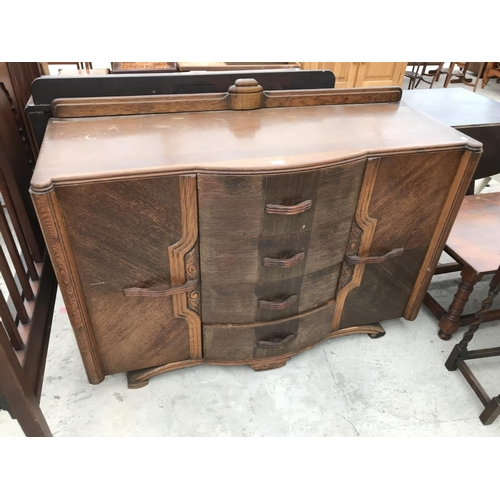 642 - AN OAK ART DECO STYLE SIDEBOARD WITH TWO DOORS AND FOUR DRAWERS...
