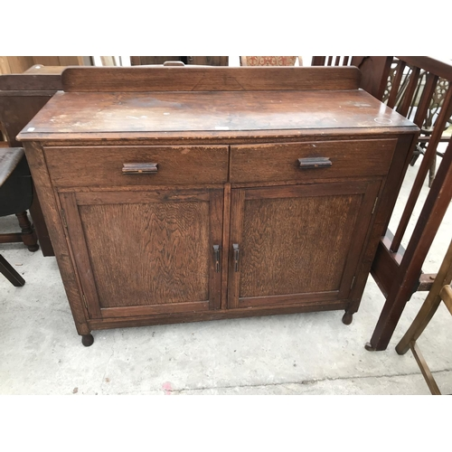 655 - AN OAK SIDEBOARD WITH TWO DOORS, TWO DRAWERS AND SPLASHBACK...